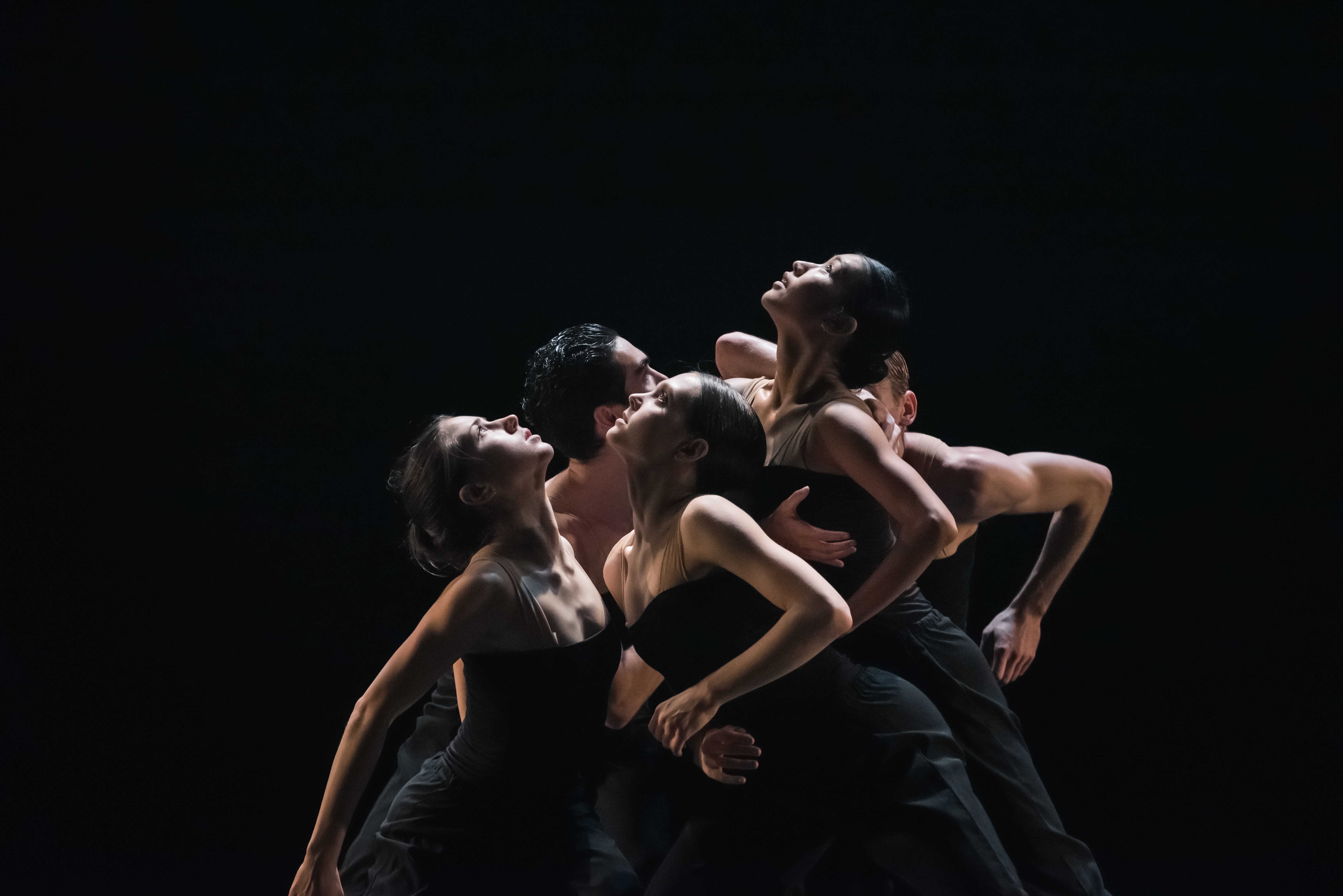 Dancer grouped together on a black stage, looking up.