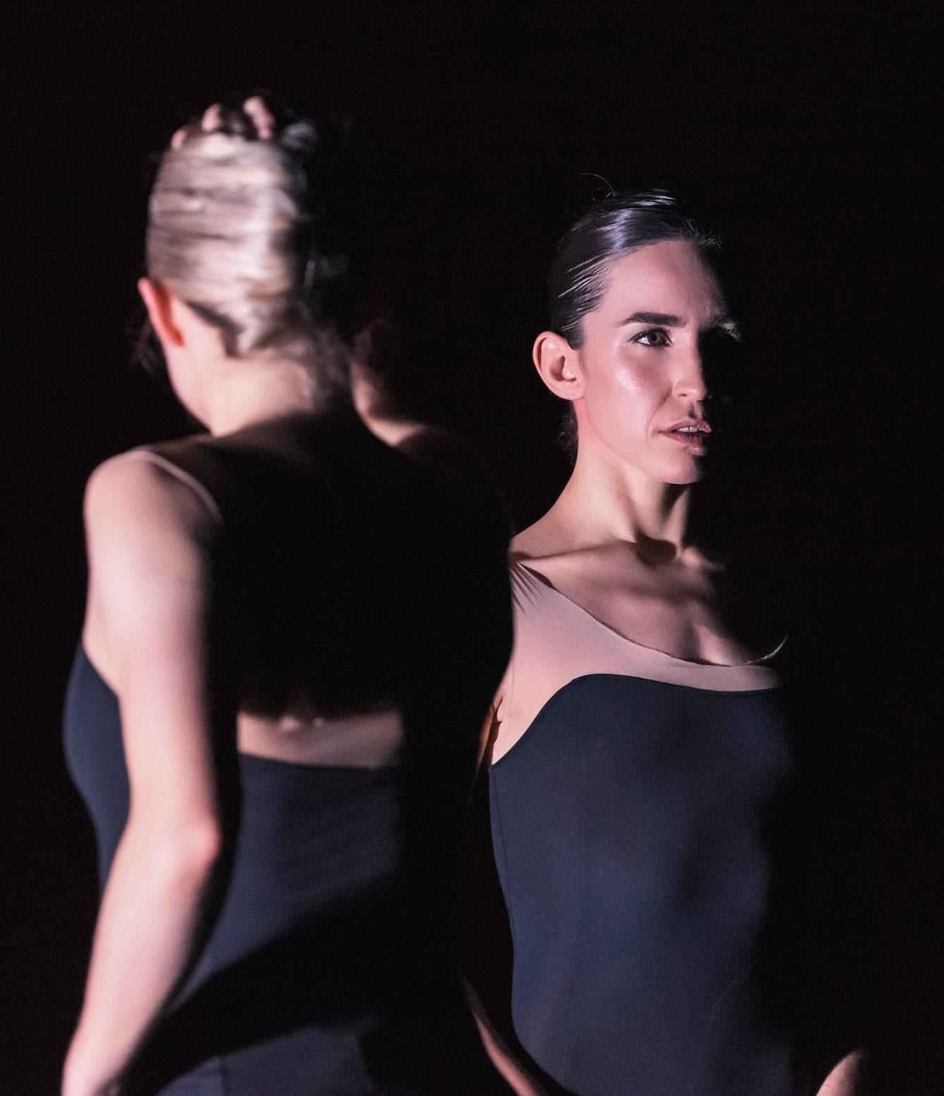 Two dancers in black bodysuits on dark stage.