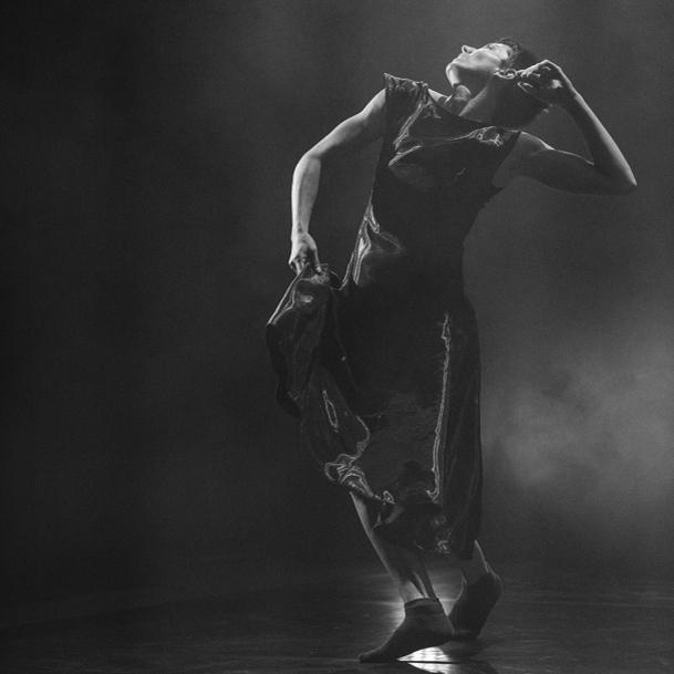 Greyscale image of Rachel Meyer dancing on stage.