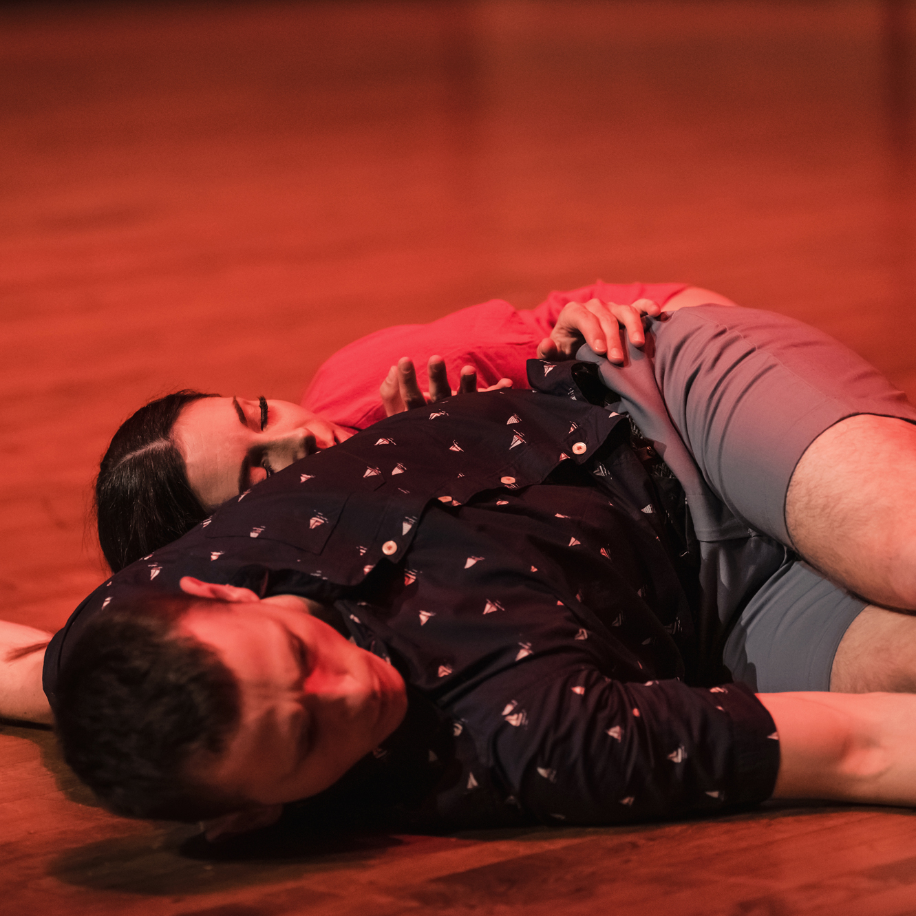 Two dancers lie on a wooden floor.